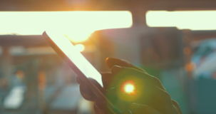 Using smart phone against bright sunlight. Close-up shot of female hands typing sms on smart phone on background of bright sun flare stock video