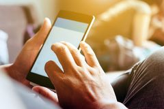 Using Smart Phone. Closeup of man hands holding and touching a smartphone Royalty Free Stock Photography