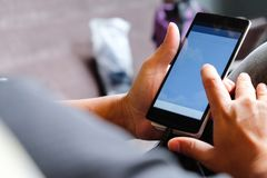Using Smart Phone. Closeup of man hands holding and touching a smartphone Royalty Free Stock Image