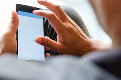 Using Smart Phone. Closeup of man hands holding and touching a smartphone Royalty Free Stock Photo