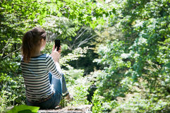 Using a smart phone in the forest Stock Photos