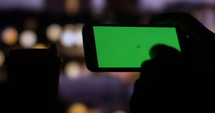 Using smart phone with Green Screen city night bokeh background. Dark silhouette close up of a mans hand using a tablet computer pc to check internet stock stock footage