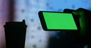 Using smart phone green screen drinking coffee tea. Dark silhouette close up of a mans hand using a tablet computer pc to check internet stock market exchange stock footage