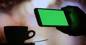 Using smart phone green screen drinking coffee tea. Dark silhouette close up of a mans hand using a tablet computer pc to check internet stock market exchange stock video