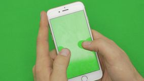 Using smart phone on green screen with various hand gestures, vertikal, close up - green screen.  stock footage