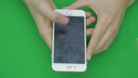 Using smart phone on green screen with various hand gestures, vertikal, close up - green screen.  stock video