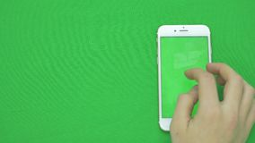 Using smart phone on green screen with various hand gestures, vertikal, close up - green screen.  stock video footage