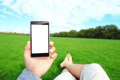 Using smart phone with nature Royalty Free Stock Photography