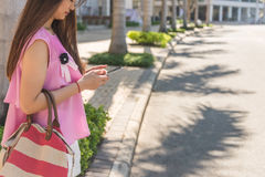 Using smart phone on the sidewalk while waiting for taxi Royalty Free Stock Photo