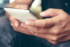 Using Smart Phone. Closeup of man hands holding and touching a smartphone Stock Images