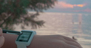 Using Smart Watch on the Beach. Closeup shot of smart watch on the wrist and stylus, calm sea is on the background stock video
