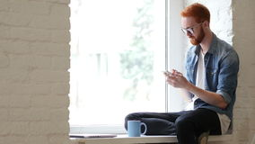 Using Smartphone, Browsing Online by Man Sitting in Window. Beard and Red Hairs, Creative designer , businessman stock video