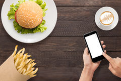 Using smartphone with burger, french fries and coffee set on the Royalty Free Stock Photography