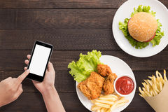 Using smartphone with burger, french fries and fried chicken set Royalty Free Stock Images