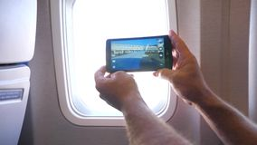 Using smartphone camera on flight. Establish shot clip stock video footage