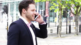 Using a Smartphone in the City. Business man in the city. He is formally dressed and is talking to someone on his smartphone stock footage