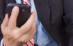 Using smartphone. Close up of businessman in action of using smartphone Stock Photo
