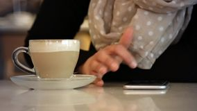 Using smartphone on coffeshop table in slow motion. Shot of Using smartphone on coffeshop table in slow motion stock footage