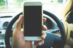 Using a smartphone while driving a car Royalty Free Stock Image