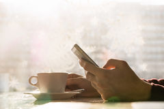 Using smartphone and having coffee at cafe Royalty Free Stock Images