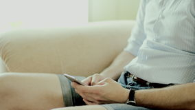Using a smartphone at home. Close up view of man's hands typing a message on a phone sitting on a sofa at home stock video