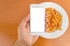 Using smartphone at the lunch time. Man holding smartphone making food photography to the meal at the table Royalty Free Stock Image