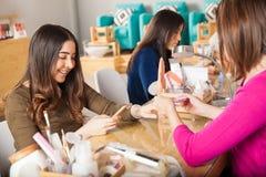 Using smartphone at a nail salon Royalty Free Stock Photos