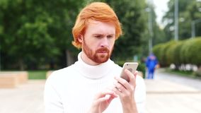 Using smartphone for online browsing, man with red hairs, outdoor. 4k, high quality stock video footage