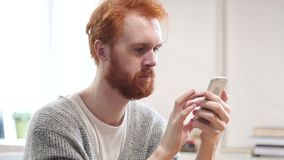 Using Smartphone for Online Browsing, Man with Red Hairs. Young creative designer , good looking stock footage