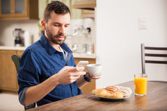Using a smartphone over breakfast Royalty Free Stock Image