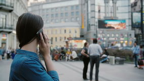 Using smartphone. Pretty young woman happily talking on the phone in a busy street. Slow mo, steadicam shot stock footage