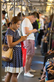 Using smartphone in public transportation Royalty Free Stock Photo