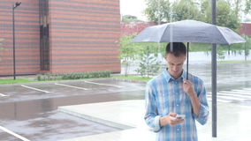 Using Smartphone, Standing Under Umbrella during Rain stock video footage