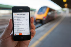 Using a Smartphone to Check Train Times and Platforms Royalty Free Stock Image