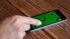 Using smartphone touchscreen. Using smartphone with green screen on wooden desk stock footage
