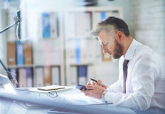 Using smartphone at workplace Stock Images