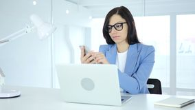 Using smartphone, young businesswoman browsing online at work. 4k, high quality stock footage