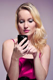 Using smartphone. Young woman holding a smartphone and is touching the screeen while looking at it. She is wearing a pink dress against a purple background Royalty Free Stock Photos