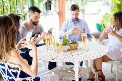 Using smartphones during a friend reunion. Five young Hispanic friends updating their social media status and texting during a reunion outdoors Stock Photo