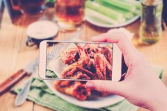 Using smartphones to take photos of BBQ wings set Royalty Free Stock Images