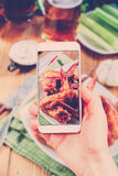 Using smartphones to take photos of BBQ wings set Stock Photo