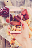 Using smartphones to take photos of Fried Potatoes and sausage Stock Images