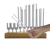 Using Sound Healing Tuning Forks. Female hand holding tuning fork with a storage rack in the background holding ten different sized tuning forks stock photo