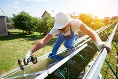 Using special drill, worker mounting solar panels on the roof. stock photography
