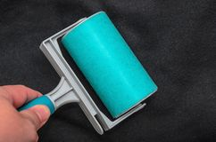 Using the sticky lint roller on a black fabric to remove dust, f. Ur, hair of the shirt. Cleaning a fabric with a washable blue sticky roller Royalty Free Stock Photography