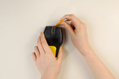 Using Stud Finder on interior home wall. Photo of female hands holding using stud finder and pencil against interior home white wall royalty free stock photo