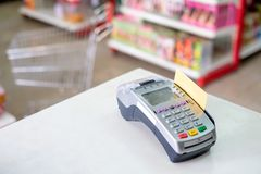 Using swiping credit card on payment terminal in store. Using swiping credit card on payment terminal in supermarket Stock Image