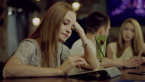 Using tablet in a bar. Young smiling woman sitting in a bar using a tablet with happy couple on background stock video
