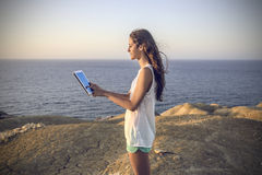 Using a tablet at the beach Royalty Free Stock Photo