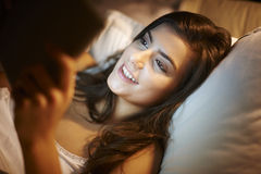 Using tablet in bed Royalty Free Stock Photo